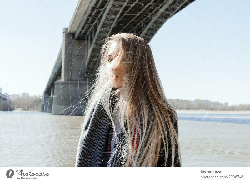 Porträt einer Frau an einem Strand mit fliegenden Haaren Ferien & Urlaub & Reisen blond Großstadt Brücke kalt Behaarung Wetter Schal Mantel Frühling Lifestyle