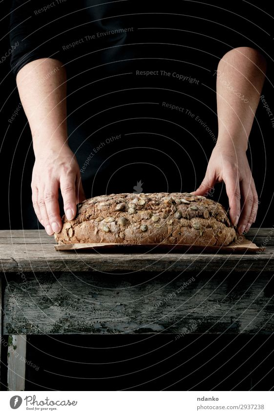 Frauenhände halten ovales, gebackenes Roggenbrot. Teigwaren Backwaren Brot Brötchen Ernährung Essen Frühstück Tisch Küche Erwachsene Hand Wärme Holz machen