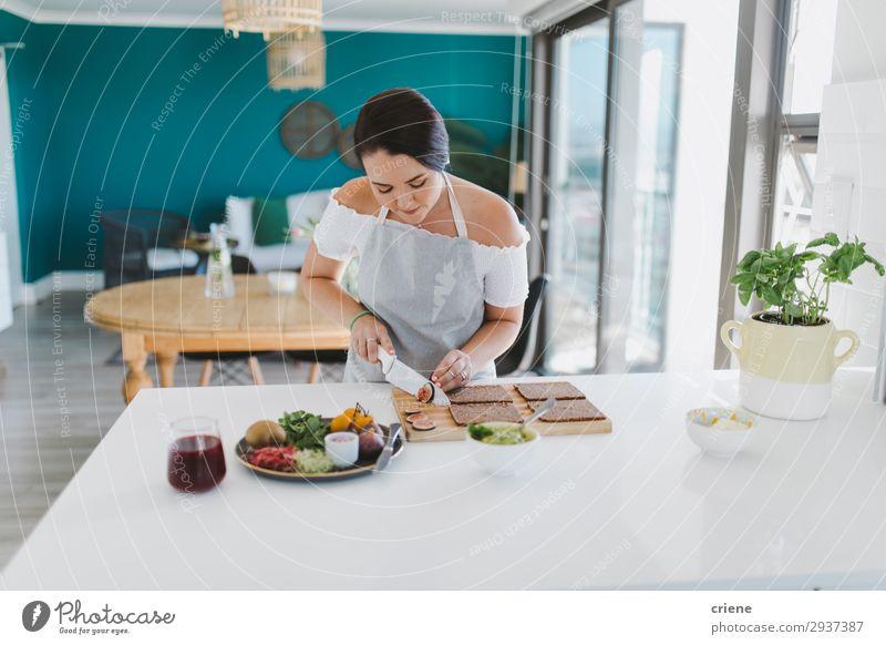 Frau beim Zubereiten von Sandwiches in der Küche Gemüse Brot Erwachsene Lächeln vorbereitend Lebensmittel Gesundheit im Innenbereich heimwärts Essen zubereiten