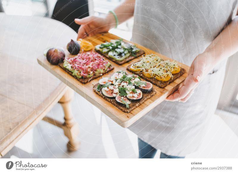 Frau, die ein Holzbrett mit gesunden Sandwiches trägt. Käse Frucht Brot Frühstück Mittagessen Hand Freude Zuprosten Belegtes Brot Gesundheit Küchenkräuter Feige