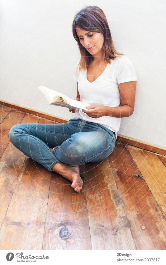 schöne Frau, die auf dem Boden sitzt und ein Buch liest. Glück lesen Schule lernen Mensch feminin Junge Frau Jugendliche Erwachsene 1 18-30 Jahre 30-45 Jahre