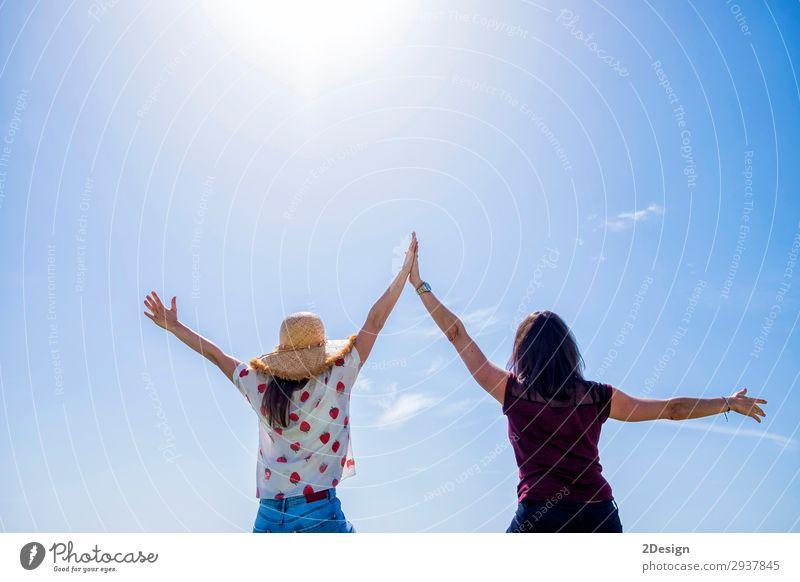 Zwei junge Frauen sitzen auf einem Zaun, die Arme sind gegen den blauen Himmel erhoben. Lifestyle Freude Glück schön Erholung Freizeit & Hobby