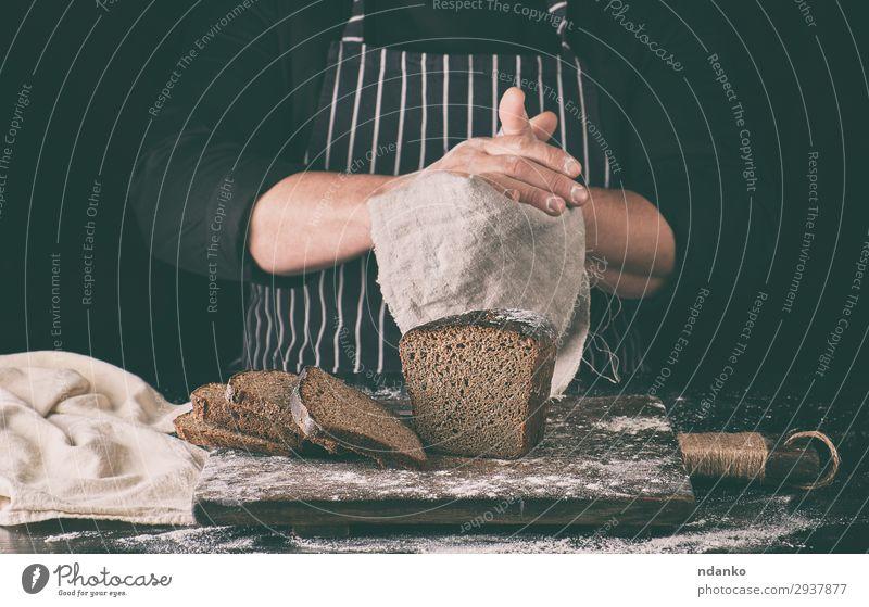 Chefkoch in schwarzem, einheitlich geschnittenem, gebackenem Roggenbrot Brot Ernährung Essen Mittagessen Abendessen Diät Tisch Küche Mann Erwachsene Hand