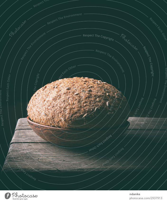 Roggenbrot mit Sonnenblumenkernen Brot Essen Frühstück Diät Teller Holz dunkel frisch lecker natürlich braun Tradition rustikal altehrwürdig rund Brotlaib