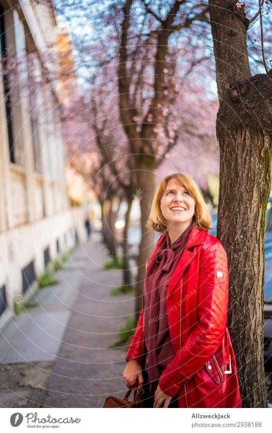 junge Frau leht an einem Baum und freut sich über Kirschblüten Ferien & Urlaub & Reisen Junge Frau Stadt rot Freude Reisefotografie Blüte Frühling Glück