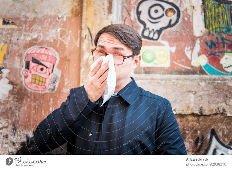 junger Mann ist krank und putzt sich die Nase Wand Porträt Junger Mann Nahaufnahme Gesicht Erkältung Krankheit Schnäuzen Taschentuch atmen Mantel