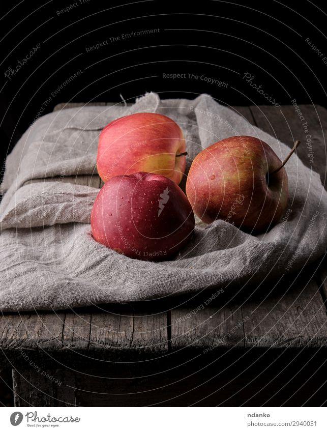 drei frische rote Äpfel lagen auf grauen Leinenservietten. Frucht Apfel Dessert Ernährung Vegetarische Ernährung Diät Tisch Natur Pflanze Herbst Holz natürlich