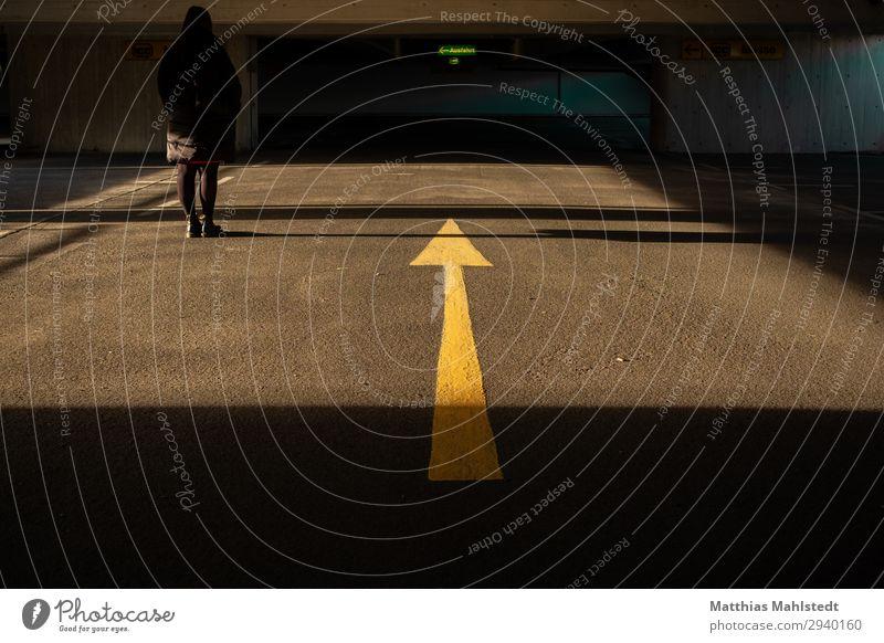 Junge Frau in einer Tiefgarage Mensch feminin Jugendliche 1 18-30 Jahre Erwachsene Parkhaus Beton Zeichen Hinweisschild Warnschild Verkehrszeichen Pfeil stehen