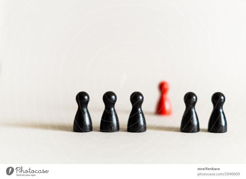 Einzelne rote Spielfigur steht abseits hinter einer Reihe von schwarzen Spielfiguren Spielen Brettspiel Menschengruppe Spielzeug Holz außergewöhnlich rebellisch