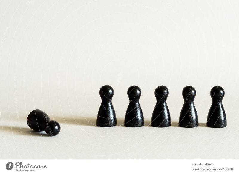 Einzelne schwarze Spielfigur liegt abseits neben einer Reihe weiterer schwarzer Spielfiguren Spielen Wirtschaft Team Arbeitslosigkeit Menschengruppe Spielzeug