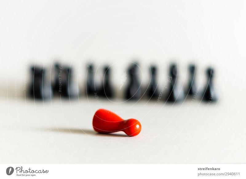 Einzelne rote Spielfigur steht vor einer Gruppe von schwarzen Spielfiguren im Hintergrund Spielen Menschengruppe Spielzeug Holz Zeichen beobachten liegen