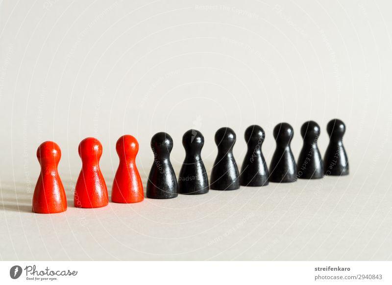 Drei rote Spielfiguren stehen mit sieben schwarzen Spielfiguren in einer Reihe Menschengruppe Spielzeug Holz ästhetisch einfach Kraft gewissenhaft Wahrheit