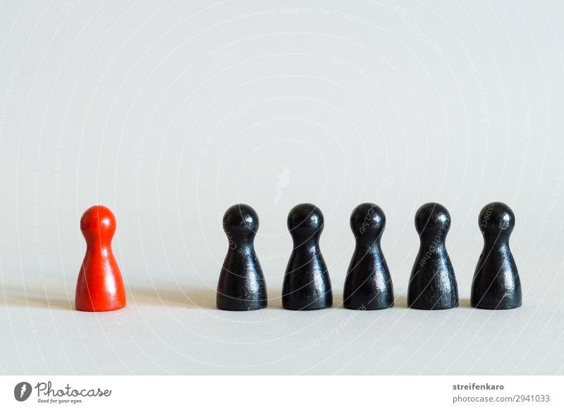 Einzelne rote Spielfigur steht abseits von einer Reihe schwarzer Spielfiguren Spielen Wirtschaft Sitzung Team Menschengruppe Spielzeug Holz Kommunizieren