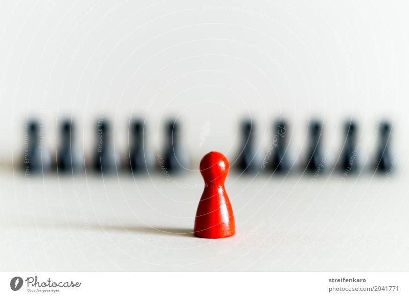 Einzelne rote Spielfigur vor einer Reihe von schwarzen Spielfiguren Freizeit & Hobby Spielen Brettspiel Wirtschaft Team Menschengruppe Zeichen wählen warten