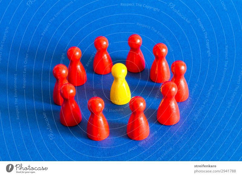 Einzelne gelbe Spielfigur steht in einem Kreis aus roten Spielfiguren auf blauem Untergrund Spielen Menschengruppe Spielzeug Holz wählen beobachten Beratung