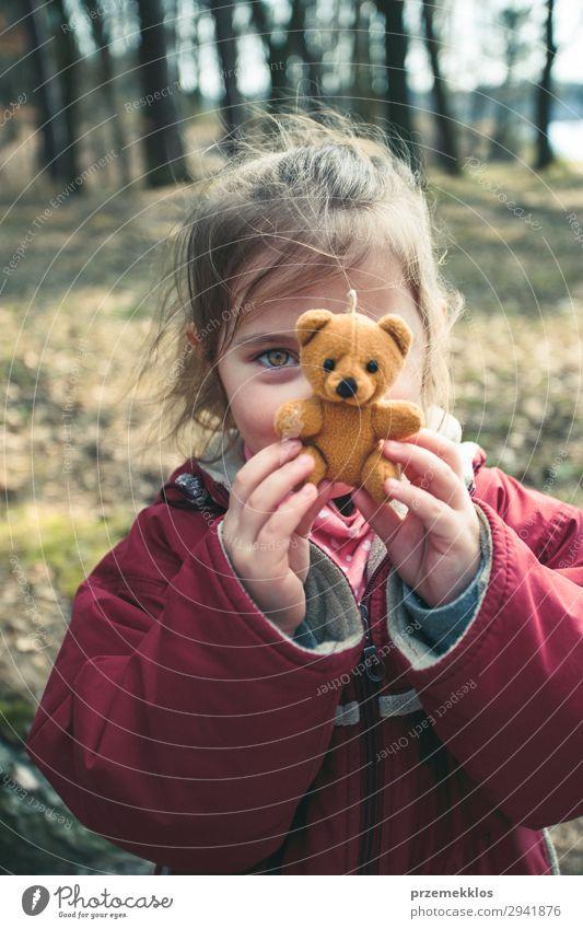 Kleines Mädchen spielt mit ihrem kleinen Teddybärenspielzeug in einem Park. Lifestyle Freude schön Spielen Sommer Kind Frau Erwachsene Kindheit Spielplatz Jacke