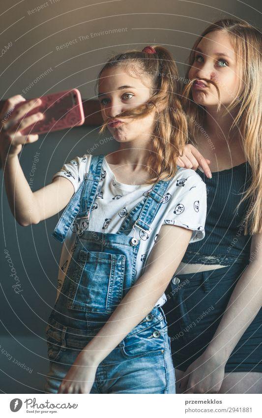 Junge Frauen bei der Selbsthilfe, mit Smartphone-Kamera. Mädchen, die Grimassen schneiden, genießen es, gemeinsam lustige Fotos zu machen Lifestyle Freude Glück