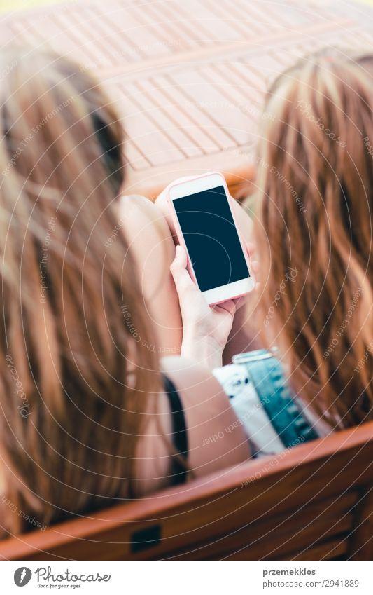 Junge Frauen, die Mobiltelefone benutzen und sich einen Musikclip ansehen. Lifestyle Sommer sprechen Telefon Handy PDA Technik & Technologie Erwachsene