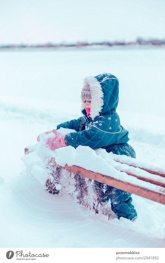 Kleines Mädchen genießt den Winter und entfernt Schnee von einer Bank. Lifestyle Freude Glück Spielen Kind Mensch Frau Erwachsene Kindheit 1 Natur Landschaft