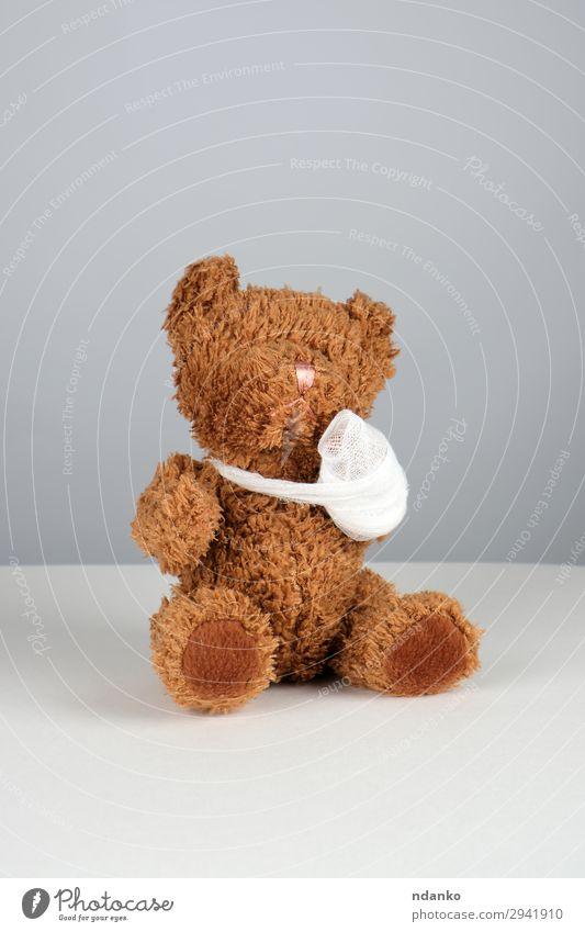 brauner Teddybär mit einer bandagierten Pfote Behandlung Krankheit Medikament Kind Krankenhaus Kindheit Arme Band Spielzeug sitzen klein lustig niedlich weiß