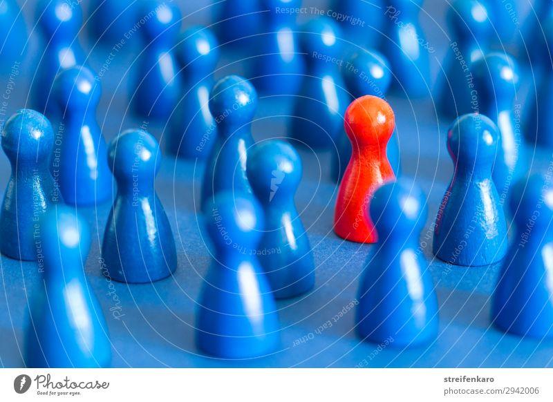 Einzelne rote Spielfigur zwischen vielen blauen Spielfiguren auf blauem Untergrund Spielen Brettspiel Menschengruppe Spielzeug Holz Zeichen wählen Zusammensein