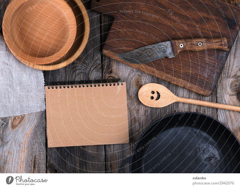 leere schwarze runde Bratpfanne, Schneidebrett Teller Pfanne Messer Löffel Tisch Küche Papier Holz Metall alt oben Sauberkeit braun grau Hintergrund Holzplatte