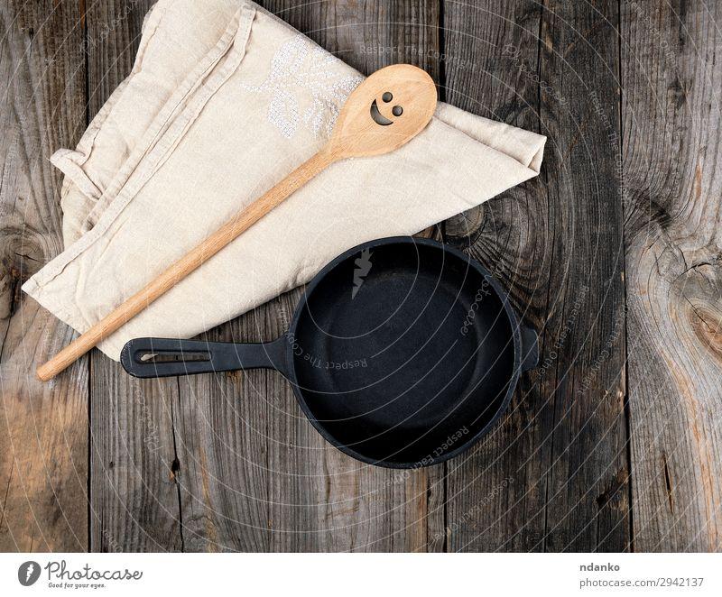 leere schwarze runde Bratpfanne Pfanne Löffel Tisch Küche Werkzeug Holz Metall alt oben Sauberkeit braun grau Hintergrund Holzplatte gießen Essen zubereiten