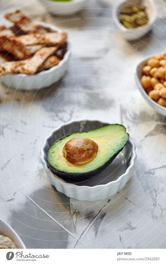 Avocado halbiert sich auf dem Tisch Lebensmittel Fleisch Gemüse Frucht Ernährung Essen Frühstück Mittagessen Bioprodukte Vegetarische Ernährung Diät exotisch