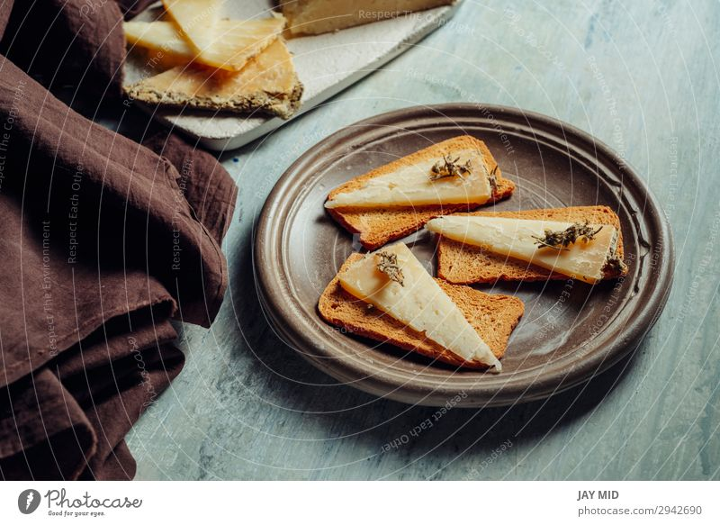 Halbgereifter Käse Rosmarin auf geröstetem Brot geschnitten Lebensmittel Bioprodukte Vegetarische Ernährung Diät Gastronomie alt dunkel frisch lecker natürlich