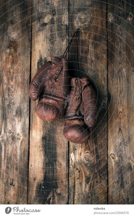 sehr alte lederne braune Boxhandschuhe hängen Lifestyle Sport Seil Leder Handschuhe Holz Fitness dreckig retro Schutz Konkurrenz Aktion antik Antiquität