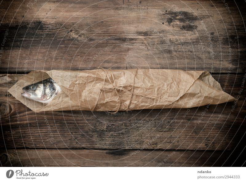 Seebarschfisch in braunem Papier eingewickelt Meeresfrüchte Ernährung Tisch Küche Seil Tier Holz Essen frisch oben grau Tasche Bass Holzplatte Essen zubereiten