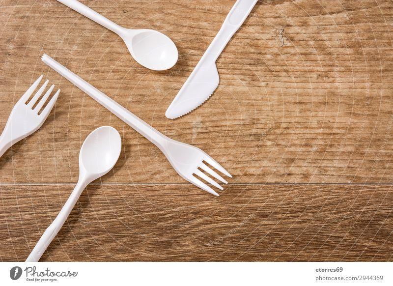 Einwegbesteck aus Kunststoff auf Holztisch. Draufsicht Küche Tisch Geschirr Recycling leer Umwelt Gabel Müll Menschengruppe industriell Geburtstag Messer