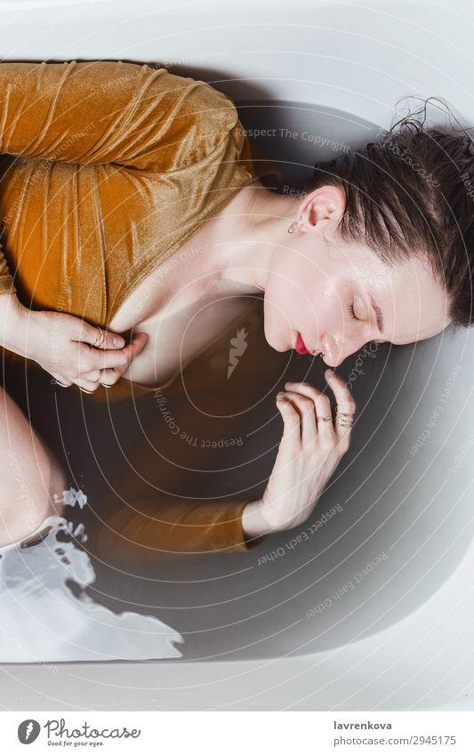Frau, die in der Badewanne liegt und mit Holzkohlewasser gefüllt ist. Schwimmen & Baden Beautyfotografie Körper Bombe Körperpflege Kaukasier Entzug Kleid
