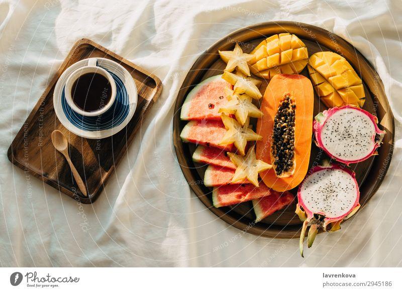 Kaffee oder Tee und tropische Obstplatte auf weißem Bett Schlafzimmer Getränk Frühstück Karambole Tasse Drachenfrucht exotisch Flachlegung Gesunde Ernährung