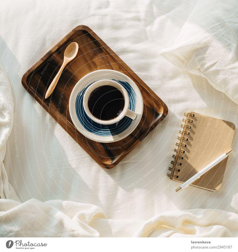 Kaffee auf Holztablett mit Notizbuch und Stift auf dem Bett Hintergrund neutral Schlafzimmer Getränk Frühstück braun Tasse flach Flachlegung heiß legen Morgen