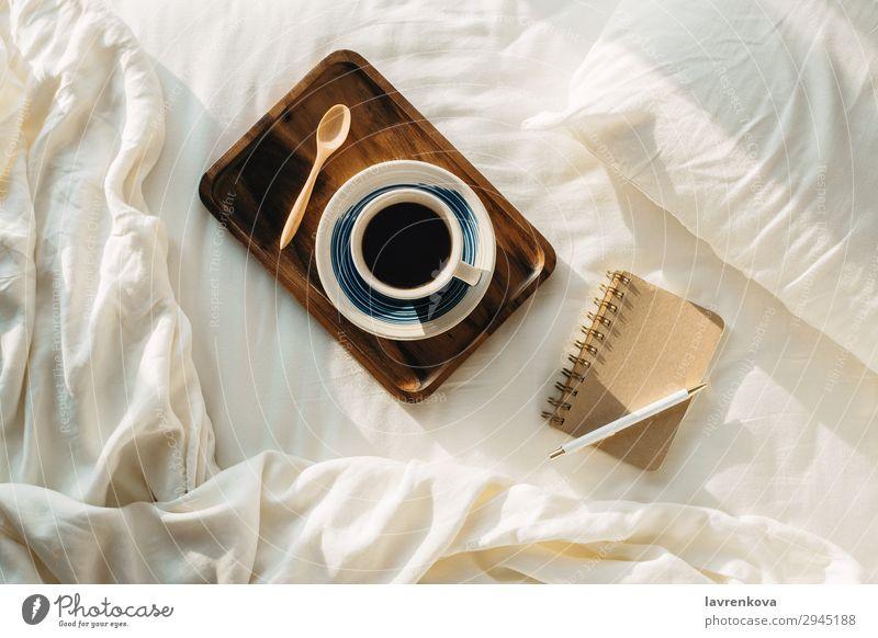 Kaffee auf Holztablett mit Notizbuch und Stift auf dem Bett Flachlegung Tablett Löffel Tee Schlafzimmer Laken Kopfkissen Schreibstift heiß Papier Tasse Becher