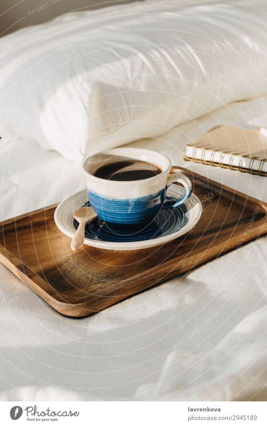 Kaffee auf Holztablett mit Notizbuch und Stift auf dem Bett Hintergrund Schlafzimmer Getränk Frühstück braun Tasse heiß Morgen Becher Papier Schreibstift