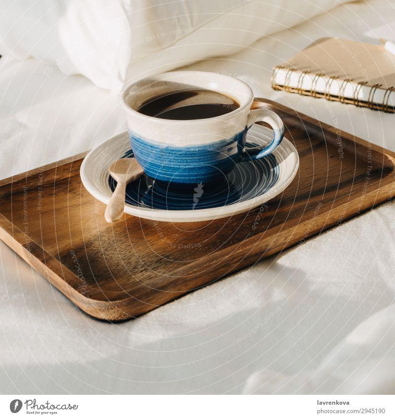 Kaffee auf Holztablett mit Notizbuch und Stift auf dem Bett Hintergrund neutral Schlafzimmer Getränk Frühstück braun Tasse heiß Morgen Becher Papier
