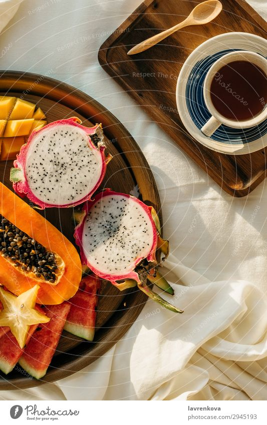 Kaffee oder Tee auf Holztablett und tropischem Obstteller exotisch Karambole Mango Pitahaya Drachenfrucht Teller Gesunde Ernährung Pflanzenbasiert
