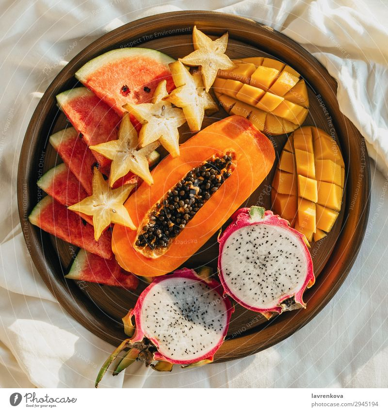 verschiedene exotische tropische Früchte auf einem Metalltablett auf dem Bett Schlafzimmer Frühstück Karambole geschnitten lecker Dessert Diät Drachenfrucht