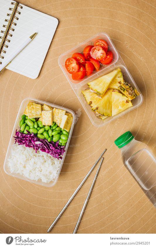 Gesunde vegane Bento-Box im asiatischen Stil Schreibstift Notizbuch Hobel Flasche Wasser Tomate geschnitten Ananas Rotkohl geschmackvoll Essen zubereiten