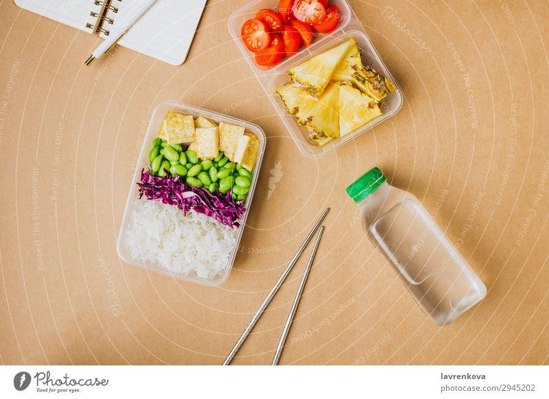 Gesunde vegane Bento-Box im asiatischen Stil Schreibstift Notizbuch Hobel Flasche Wasser flache Verlegung Tomate geschnitten Ananas Rotkohl geschmackvoll