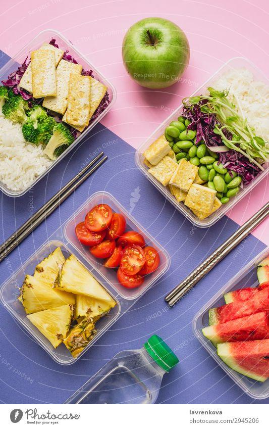 Zwei gesunde vegane Lunch-Bento-Boxen im asiatischen Stil Flasche Anklopfen Apfel Flachlegung Asiatische Küche Asiatische Reistafel Brokkoli Tomate Container