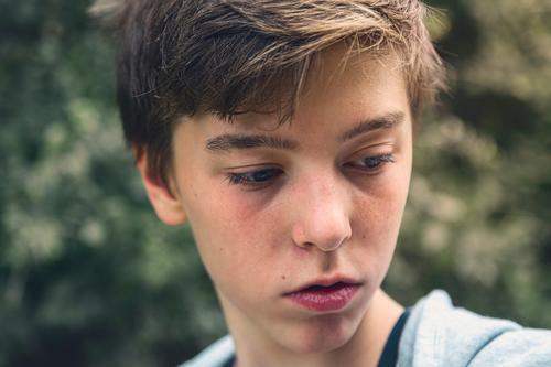 Porträt eines jungen Mannes, der gedankenverloren nach unten blickt besinnlich Teenager ernst nachdenklich Konzentration Blick Junge männlich schön lässig