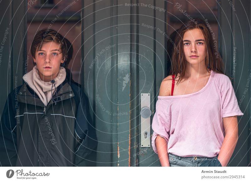Porträt eines Jungen und eines Mädchens vor einer grünen Tür Teenager Jugendliche zwei Person selbstbewusst Straße im Freien Eingang lässig jung Frau Mann