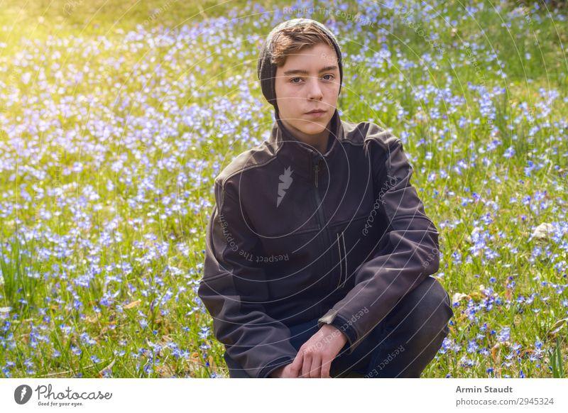 Porträt eines Jungen, der auf einer Frühlingswiese mit vielen Blumen kauert Mann männlich jung hockend Wiese im Freien Sonnenlicht blau Natur Gras grün Park