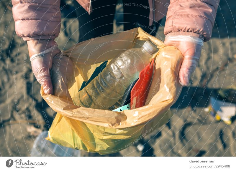 Frau, die den vom Strand gesammelten Müll zeigt. Kind Arbeit & Erwerbstätigkeit Mensch Erwachsene Hand Umwelt Sand Kunststoff dreckig Teamwork zeigen Müllsäcke