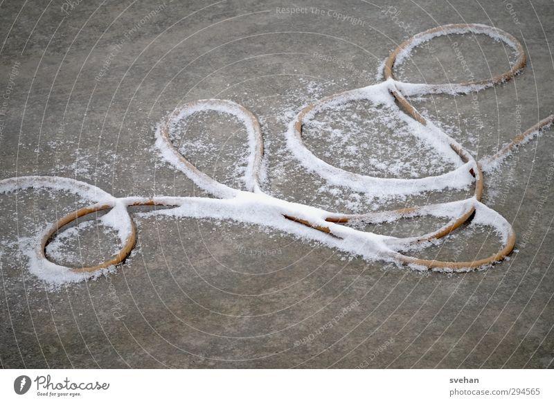 Schlängelndes Etwas Kabel Seil Beton Linie Schleife liegen grau weiß Schnee Schlaufe Winter Stromkabel durcheinander unordentlich Schlangenlinie Farbfoto