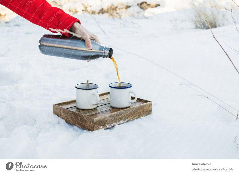 Männliche Hand, die heißen Kaffee oder Tee in eine Email-Tasse gießt. Getränk Kasten kalt Emaille Frost gefroren wandern Halt Mann Metall Becher Natur