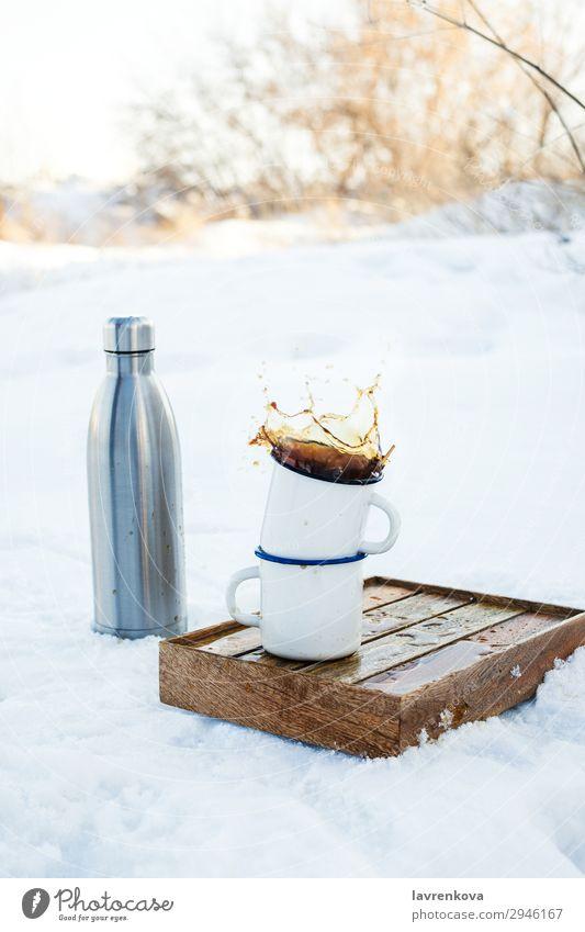 Zwei emaillierte Tassen mit spritzendem Kaffee im Freien. Ferien & Urlaub & Reisen Becher Emaille platschen Herbst Außenaufnahme Tablett Kasten wandern Picknick